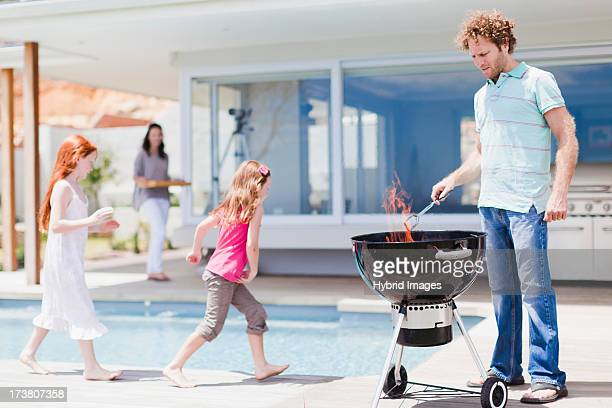 Girls around pool as father grills