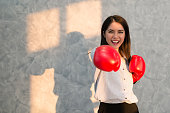 Girls Asian businessman wearing boxing gloves red hand displaying the symptoms I'm delighted winner. Business Success  concept