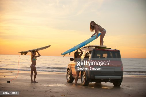 girls at beach putting surfboards on car top : Stock Photo