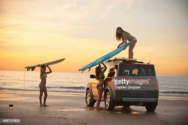 girls at beach putting surfboards on car top
