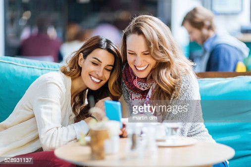 Girls at cafe text messaging on smartphone