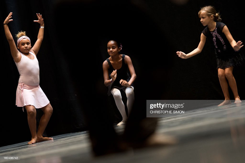 Girls attend a classic dance class given by teachers from the Royal Opera House to children from Brazilian dance schools and from shantytowns, at the Municipal Theater in Rio de Janeiro, on February 23, 2013. The Royal Opera House of London landed in Rio this week with educational programs and events that include dance lessons for children living in the city's shantytowns. AFP PHOTO/Christophe Simon