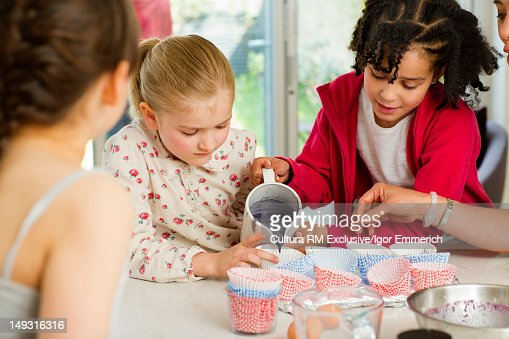 Girls baking together in kitchen : Stock Photo