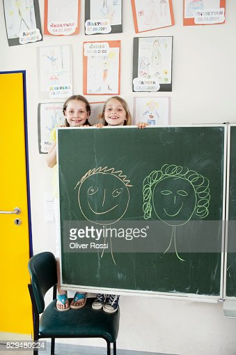 Girls behind blackboard in classroom : Stock Photo
