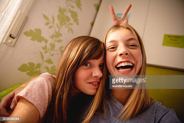 Girls being silly in colourful bedroom while posing for camera