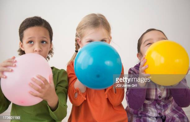 Girls blowing balloons together