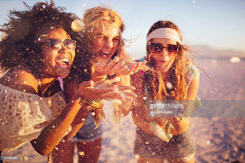 Mädchen Blasen Konfetti von Ihren Händen auf einem Strand : Stock-Foto