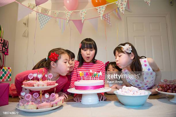 Girls blowing out birthday candles on cake