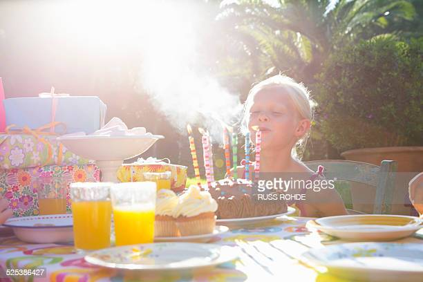 Girls blowing out candles on birthday cake