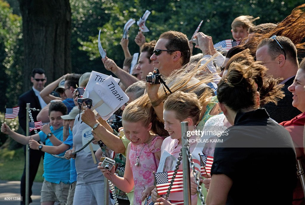 A girl's blows in the wind as presidential helicopter Marine One lands on the South Lawn as US President George W. Bush and First Lady Laura Bush arrive at the White House in Washington on July 20, 2008. Bush spent the weekend at his ranch in Crawford, Texas. AFP PHOTO/Nicholas KAMM