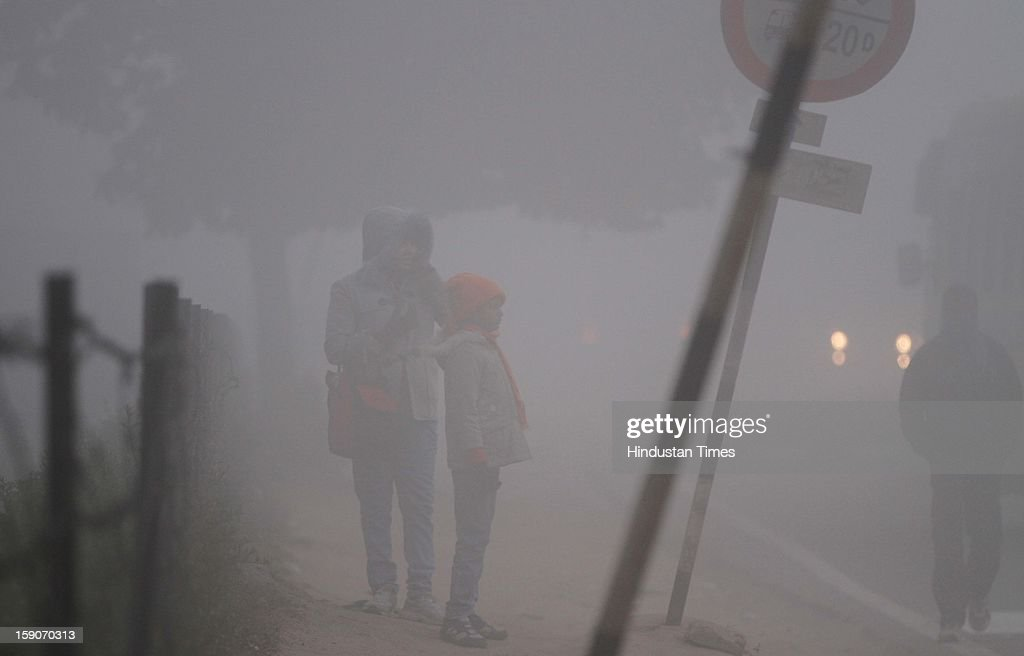 Girls braving cold and foggy morning on January 7, 2013 in New Delhi, India. Dense fog and icy winds disrupted normal life as Delhi's minimum temperature settled at five notches below average at 2.4 degrees Celsius. Fog forced visibility to drop to about 500 metres in the morning resulting in 15 flights and 42 trains were delayed out of Delhi while 18 trains got cancelled.