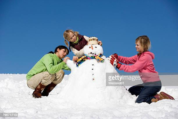 Girls building snowman