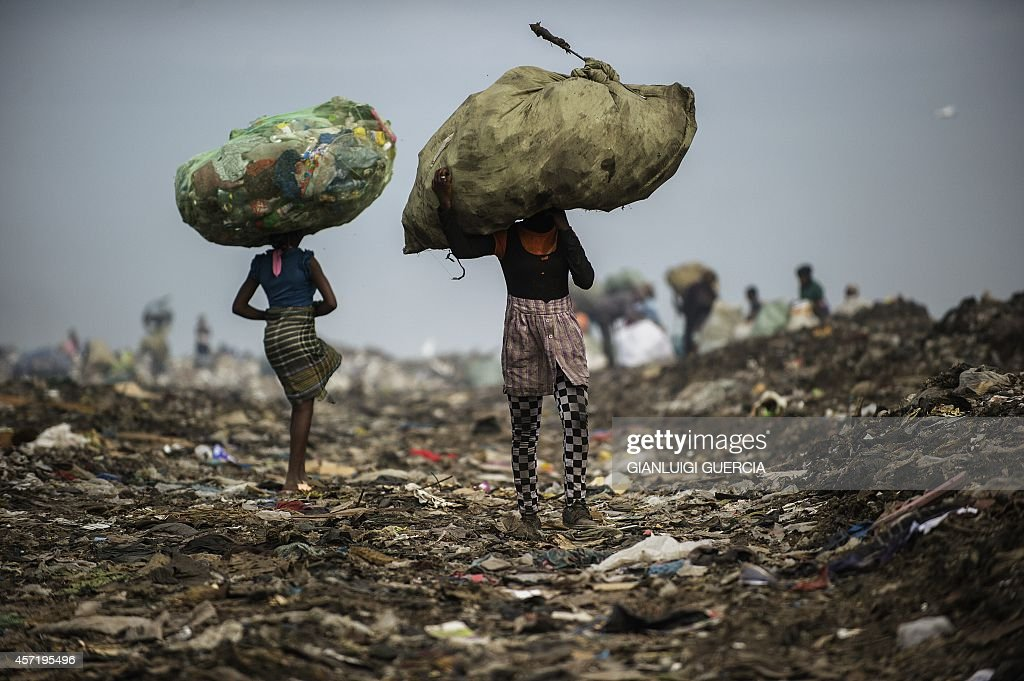 Girls carry bags of plastic items and tins as rubbish pickers sift through garbage at the Maputo municipal garbage dumping site in Maputo on October 14, 2014. Mozambique's upstart opposition vowed to take on the two traditional political heavyweights by offering a non-violent alternative in polls taking place on October 15 after a low-level conflict.