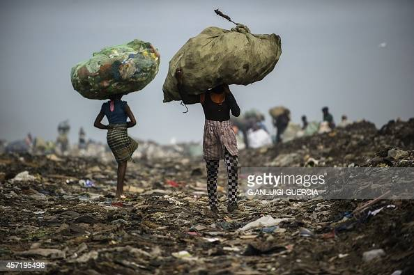 Girls carry bags of plastic items and tins as rubbish pickers sift through garbage at the Maputo municipal garbage dumping site in Maputo on October...
