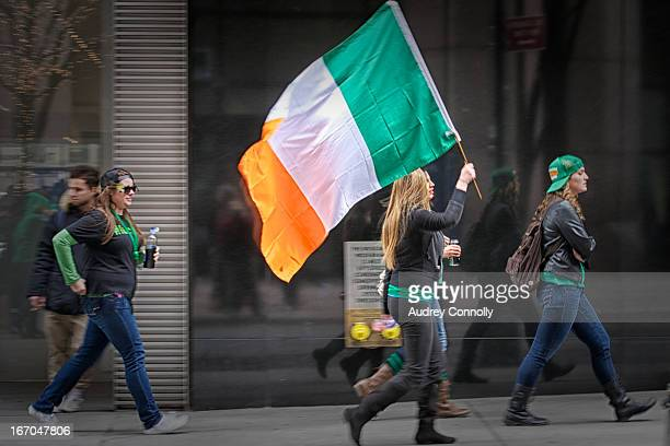 CONTENT] girls carrying Irish Flag through streets of New York during the annual Saint Patrick's Day Parade in Midtown Manhattan New York City