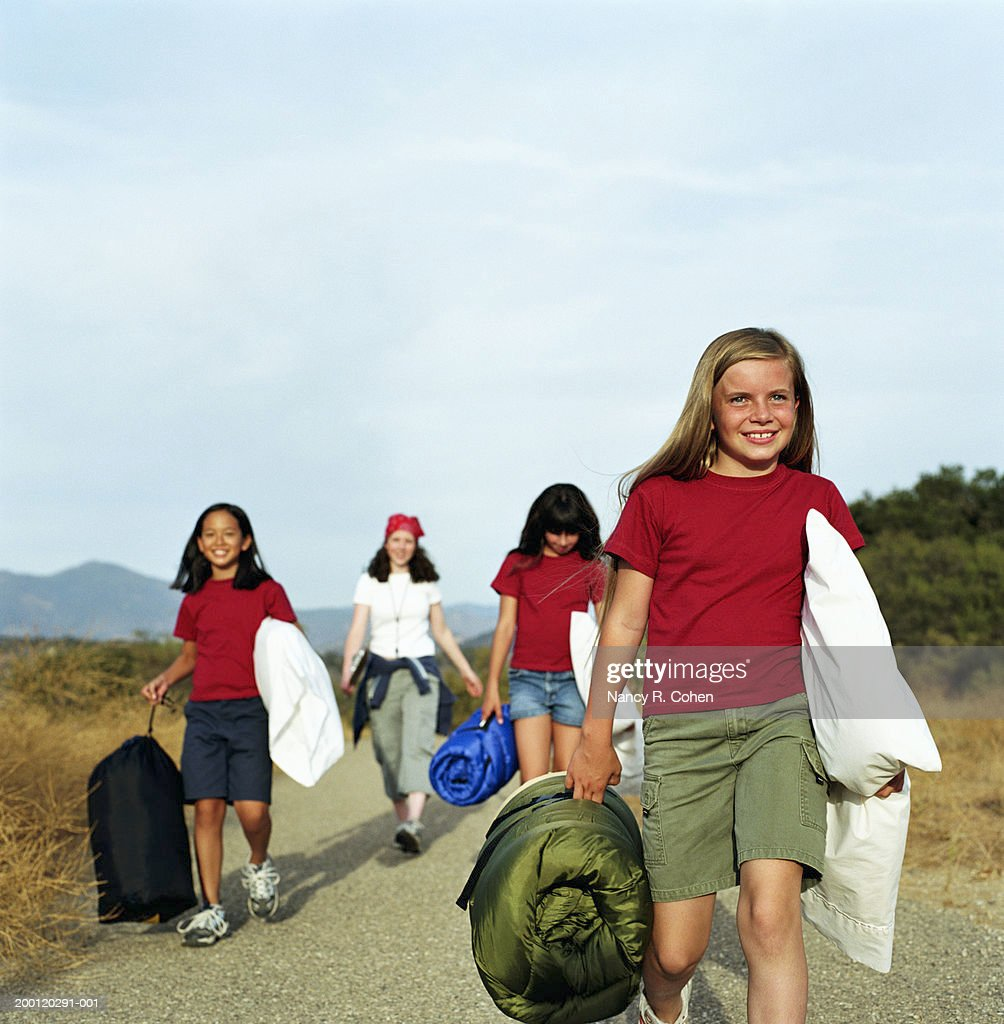 Girls (8-10) carrying sleeping bags and pillows : Stock Photo