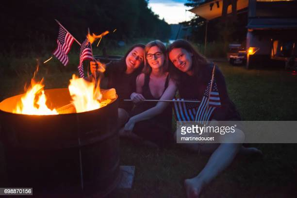 Girls celebrating Independence day with campfire at dusk.