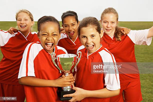 Girls celebrating victory with a trophy