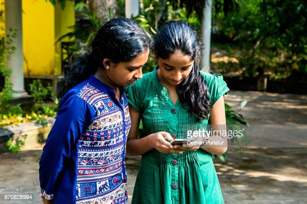 Girls checking cellphone images