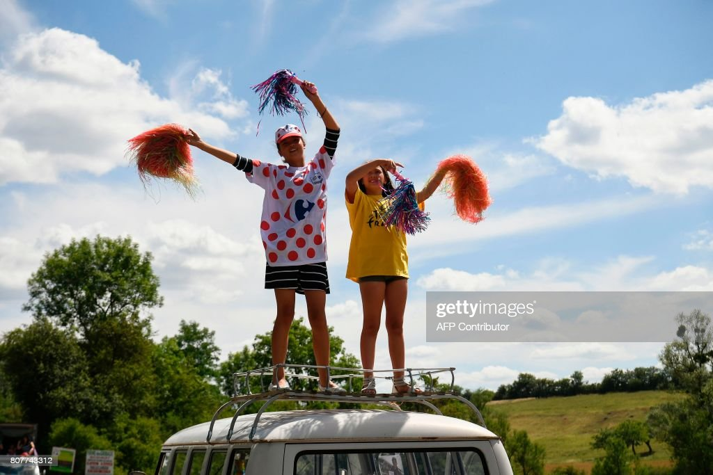 Girls cheer along the road during the 207,5 km fourth stage of the 104th edition of the Tour de France cycling race on July 4, 2017 between Mondorf-les-Bains and Vittel. / AFP PHOTO / Lionel BONAVENTURE
