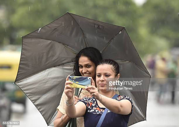 Girls clicking selfie with an umbrella during rain at Connaught Place on May 23 2016 in New Delhi India Sudden rains brought respite for people in...