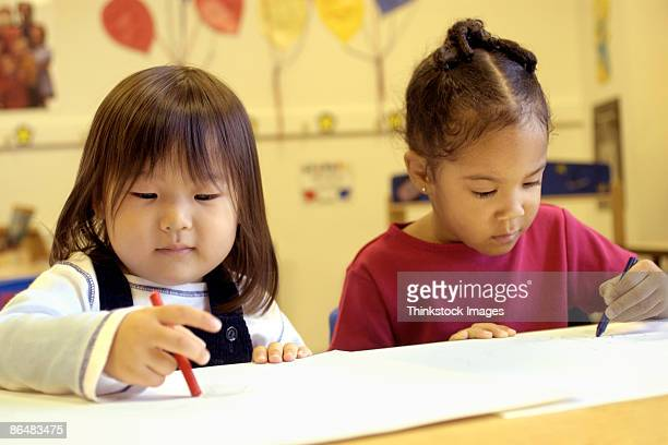 Girls coloring in pre-school
