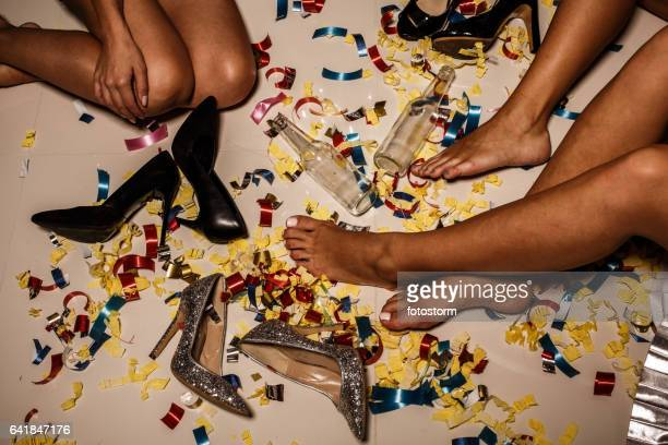 Girls, confetti, shoes and bottles on the floor after party