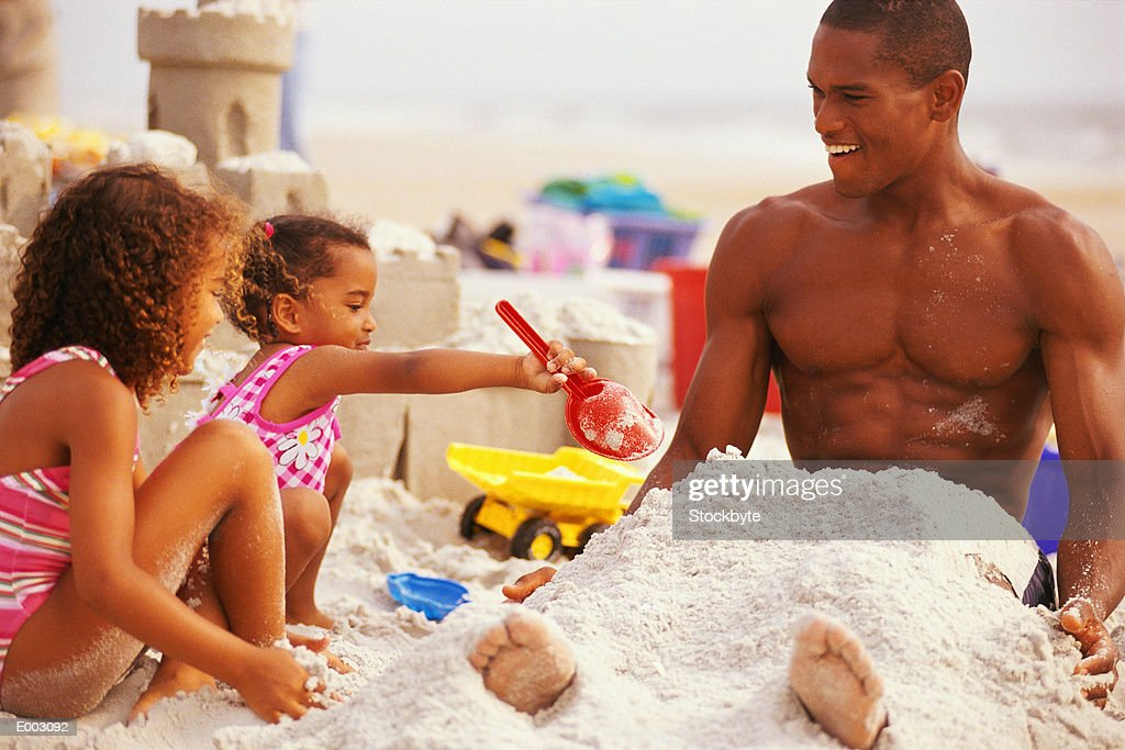 Girls covering father with sand at beach