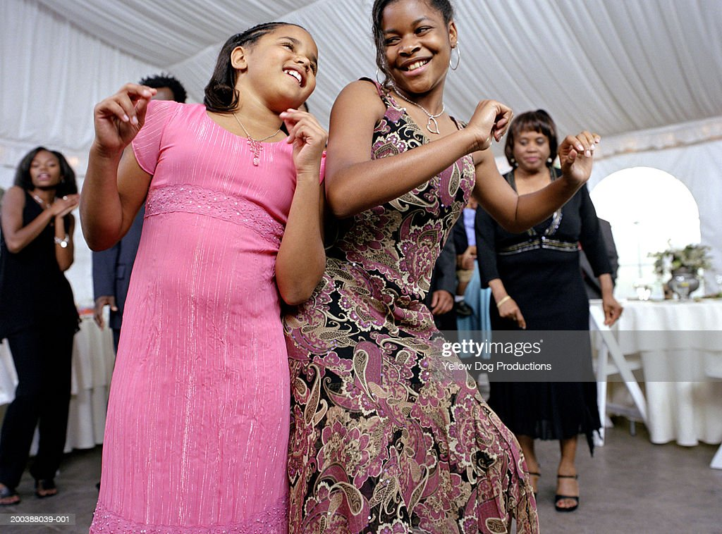 Girls (8-15) dancing at family celebration : Stock Photo