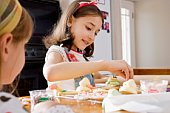 Girls decorating cookies in kitchen