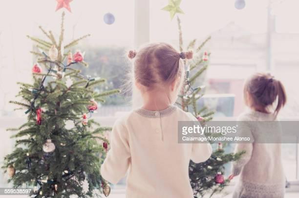 Girls decorating small Christmas trees
