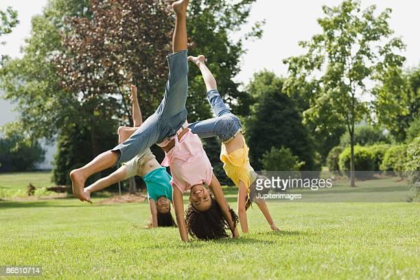 Girls doing cartwheel in field