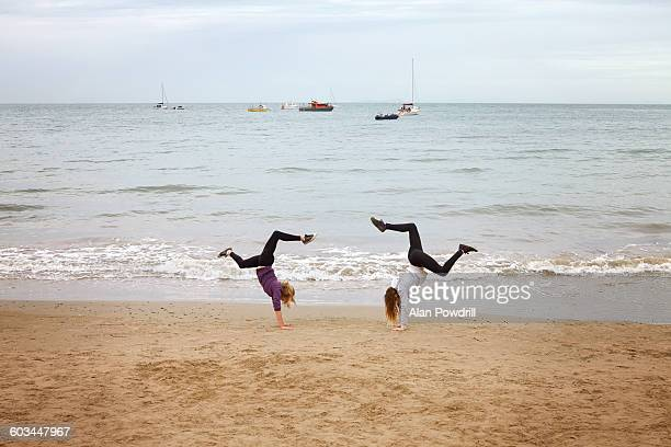2 girls doing hand stands on beach