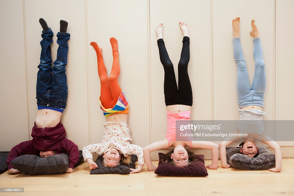 Girls doing headstands against wall : Stock Photo
