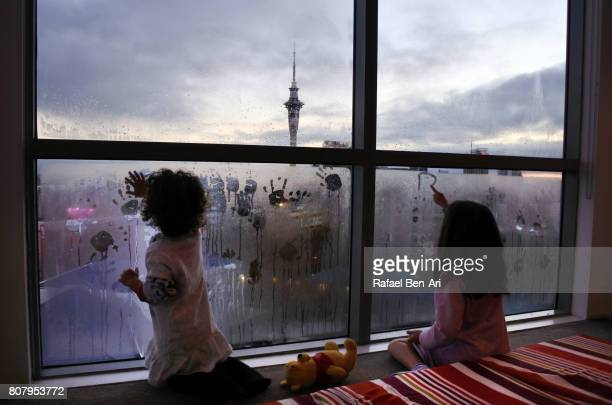 Girls drawing early morning art on window condensation