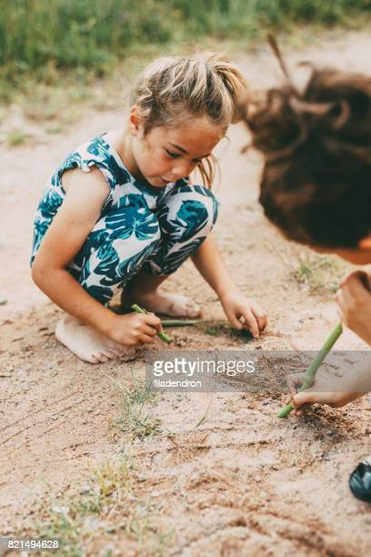 Girls drawing in the soil outdoors