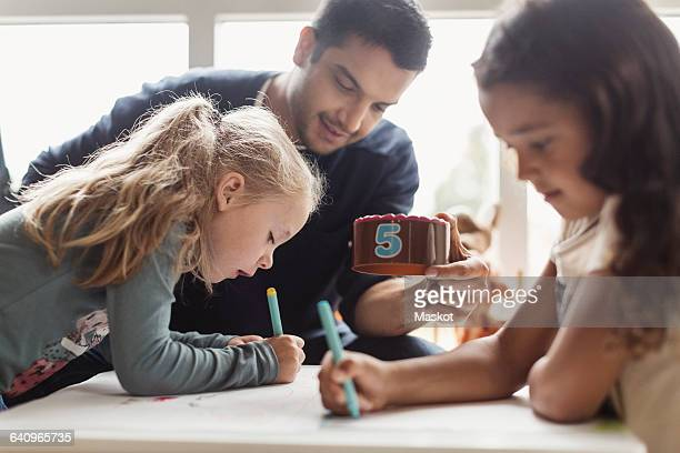 Girls drawing while male teacher holding number block in classroom