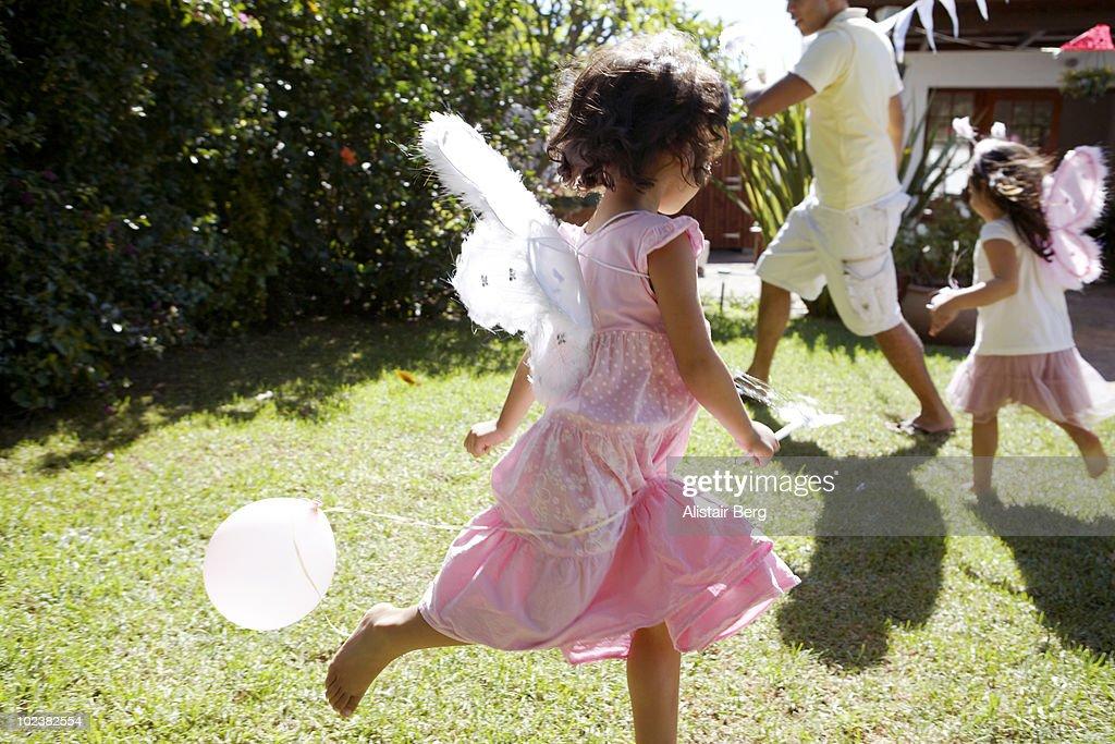 Girls dressed as fairies, running in garden : Stock Photo