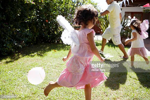 Girls dressed as fairies, running in garden