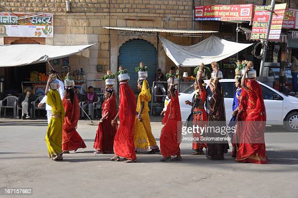 CONTENT] Girls dressed in beautiful saris walk in a parade through the streets of Jaisalmer Rajasthan India