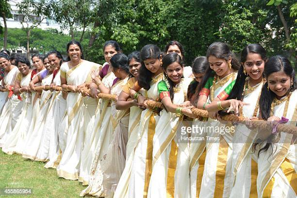 Girls dressed in traditional saree participate in tugofwar organized by Keraleeya Samajam as part of Onam celebration on September 21 2014 in Indore...