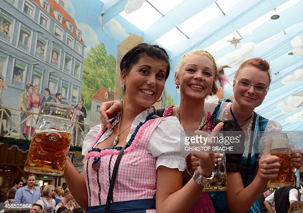 Girls dressed in typical Bavarian Dirndl dresses pose with beer mugs in a festival beer tent of the Oktoberfest beer festival at the Theresienwiese...