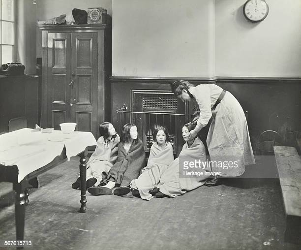 Girls drying their hair by the fire after a bath Chaucer LCC Cleansing Station London 1911 Four girls wrapped in blankets drying by a fire after...
