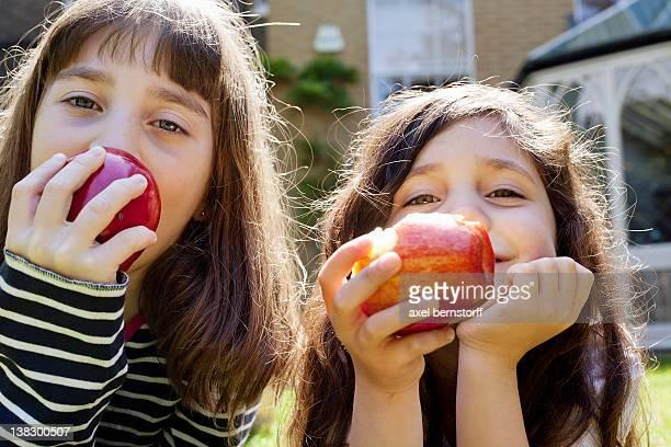 Girls eating apples outdoors