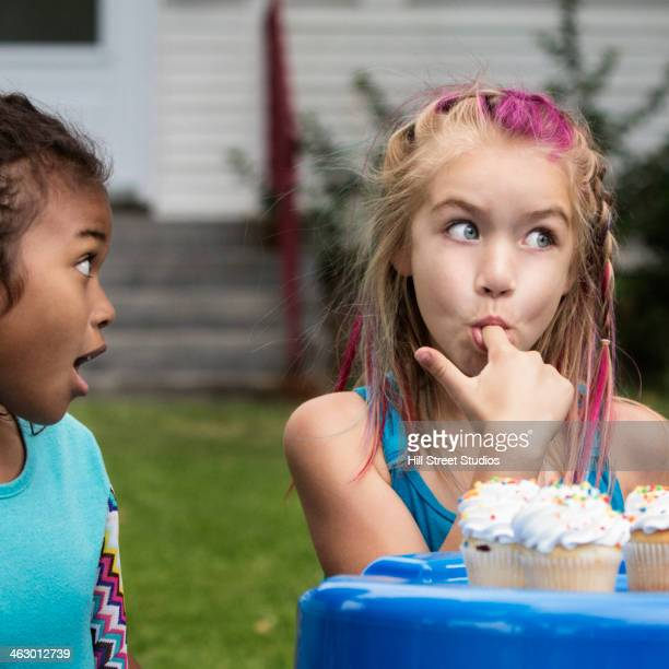 Girls eating cupcakes in backyard
