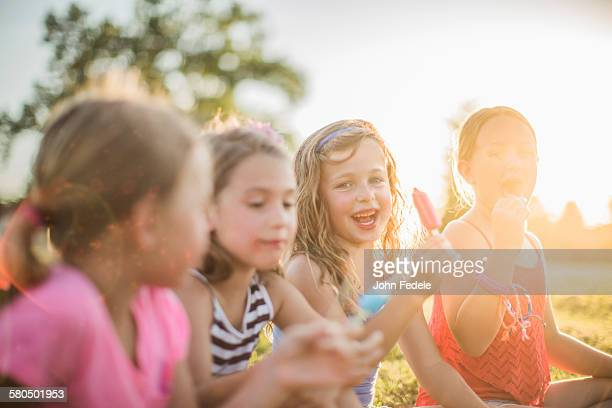 Girls eating flavored ice in sunny field