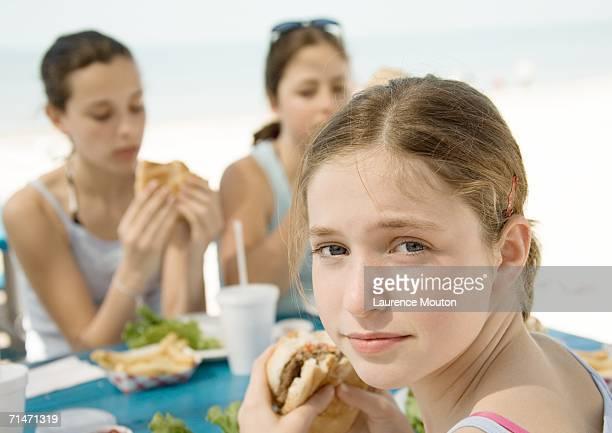 Girls eating hamburgers next to beach