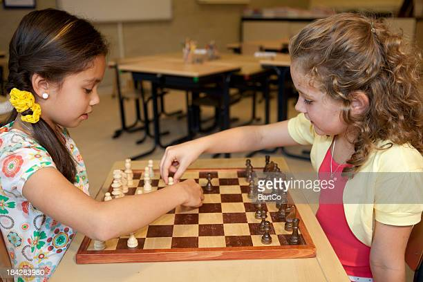 Girls, elementary age, playing chess.