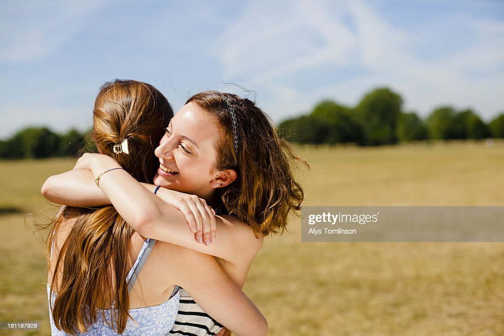 Girls embracing outside in the sun on a common : Stock Photo