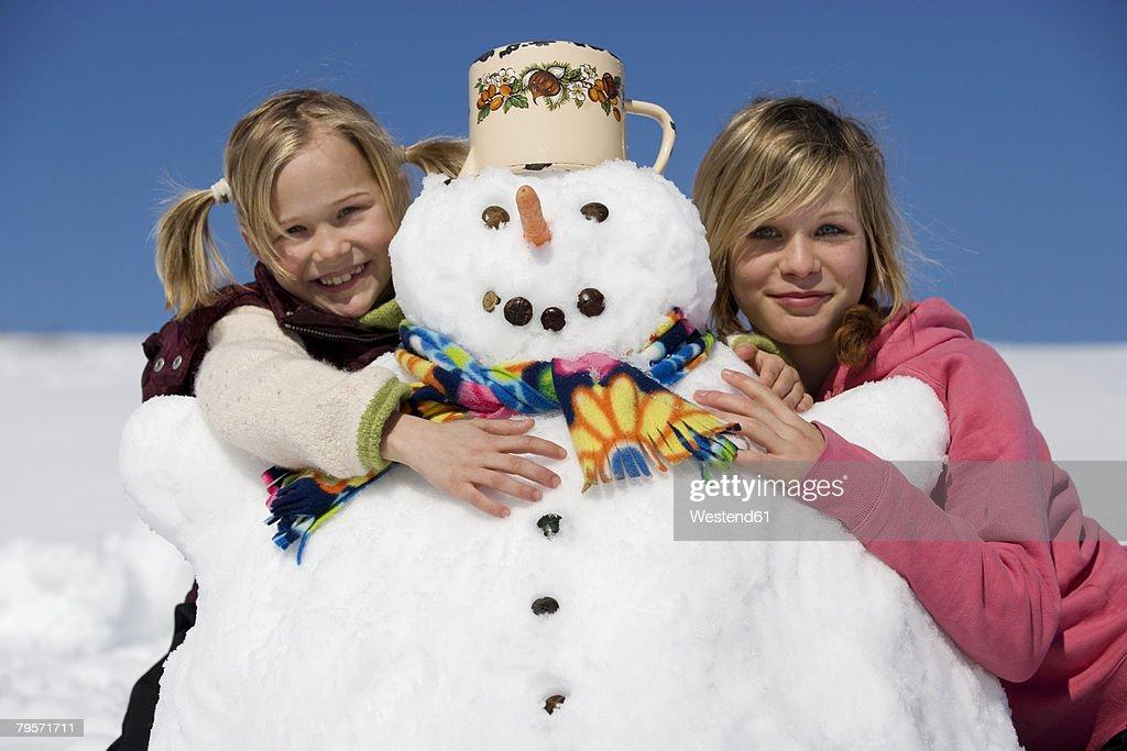Girls embracing snowman : Stock Photo